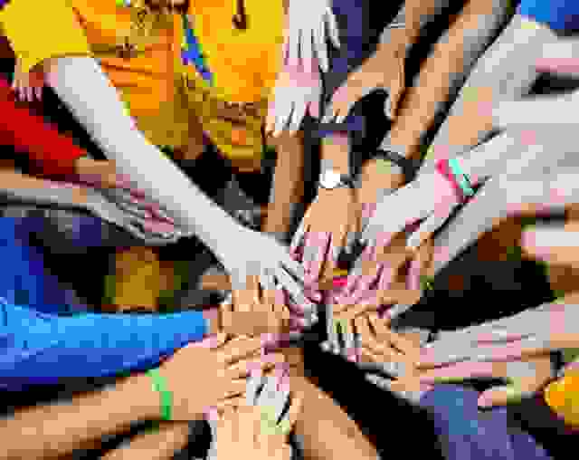 Group of camper's hands joined in the middle