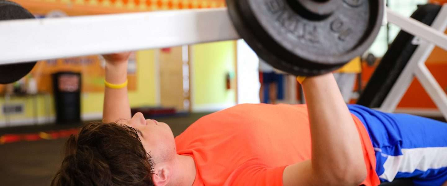 Male camper lifting weights