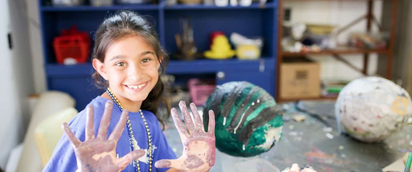 Female camper with hands covered in paint