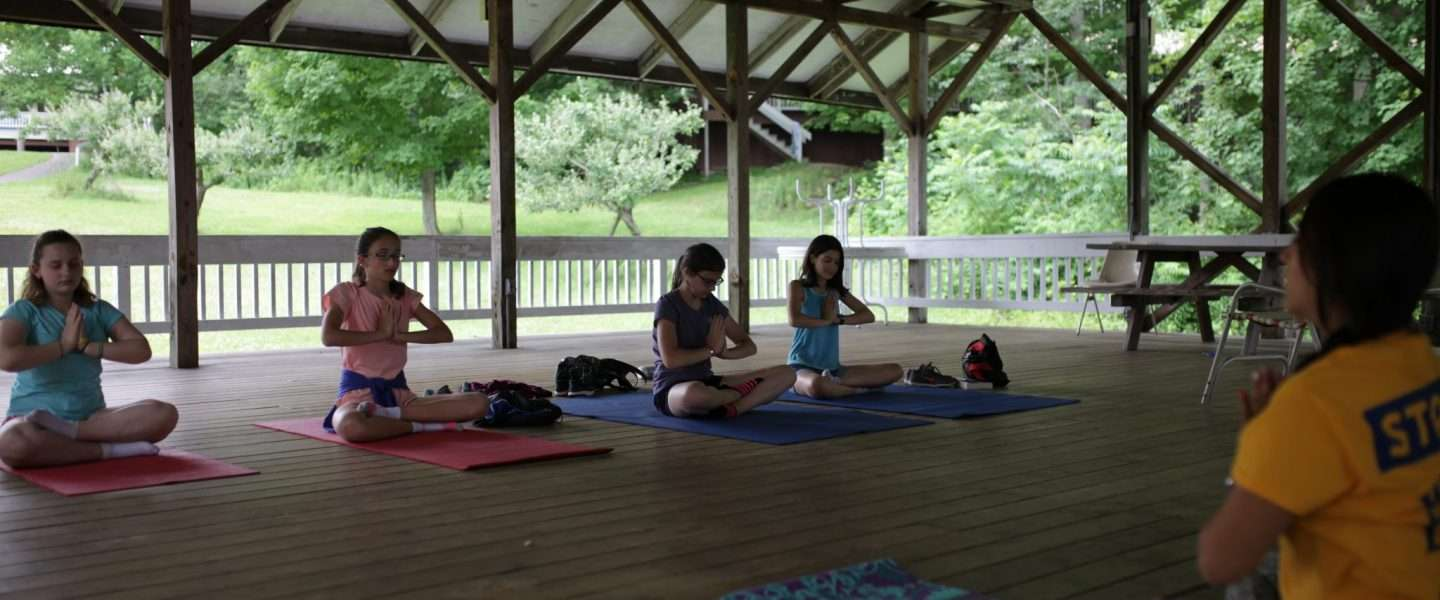Campers doing Yoga in the covered pavillion