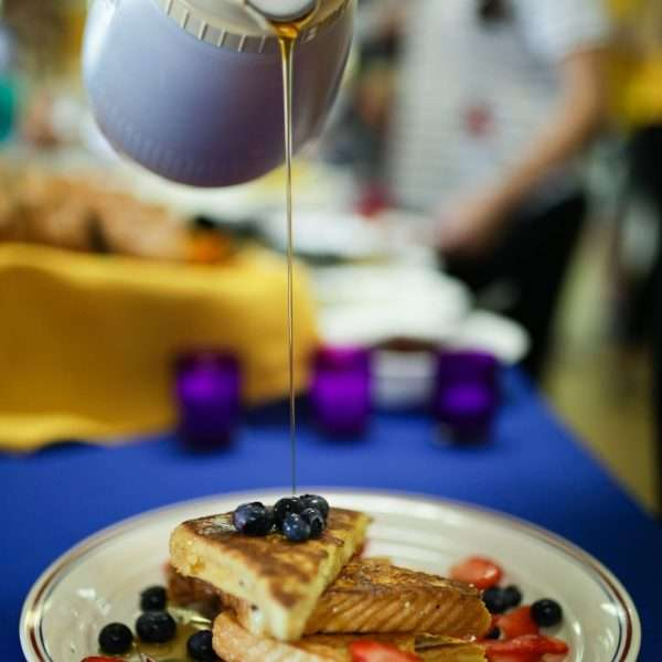 Syrup being poured onto pancakes and fruit