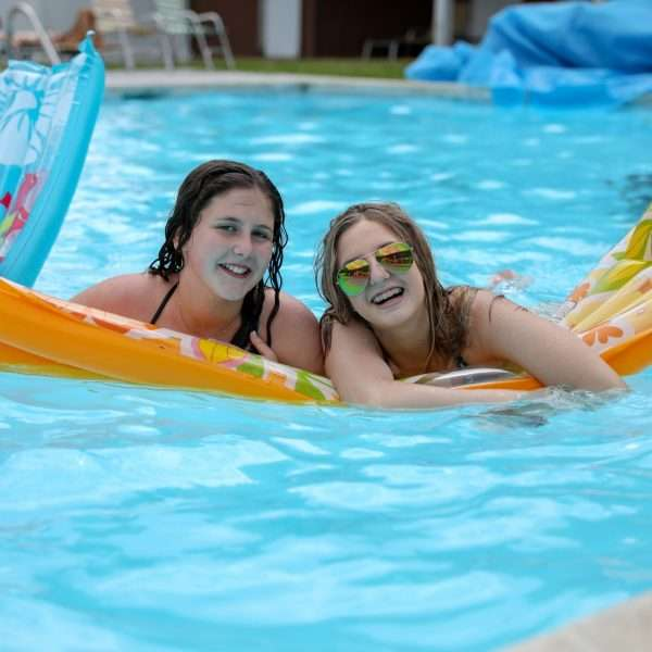 Two female campers floating on a lilo in the pool