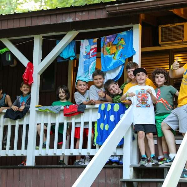 Group of young male campers hanging out on the balcony of their camper housing