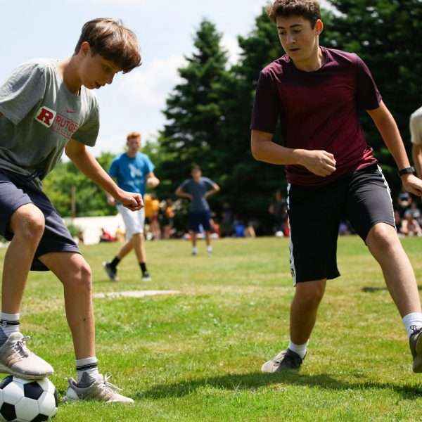 Group of campers playing soccer on the playing fields