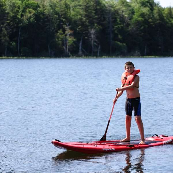 Male camper in the middle of the lake on a Paddleboard
