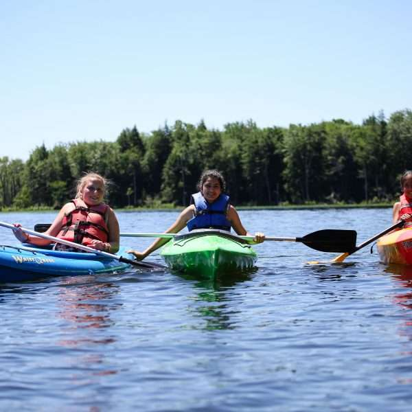 Three campers in canoes in the middle of the lake