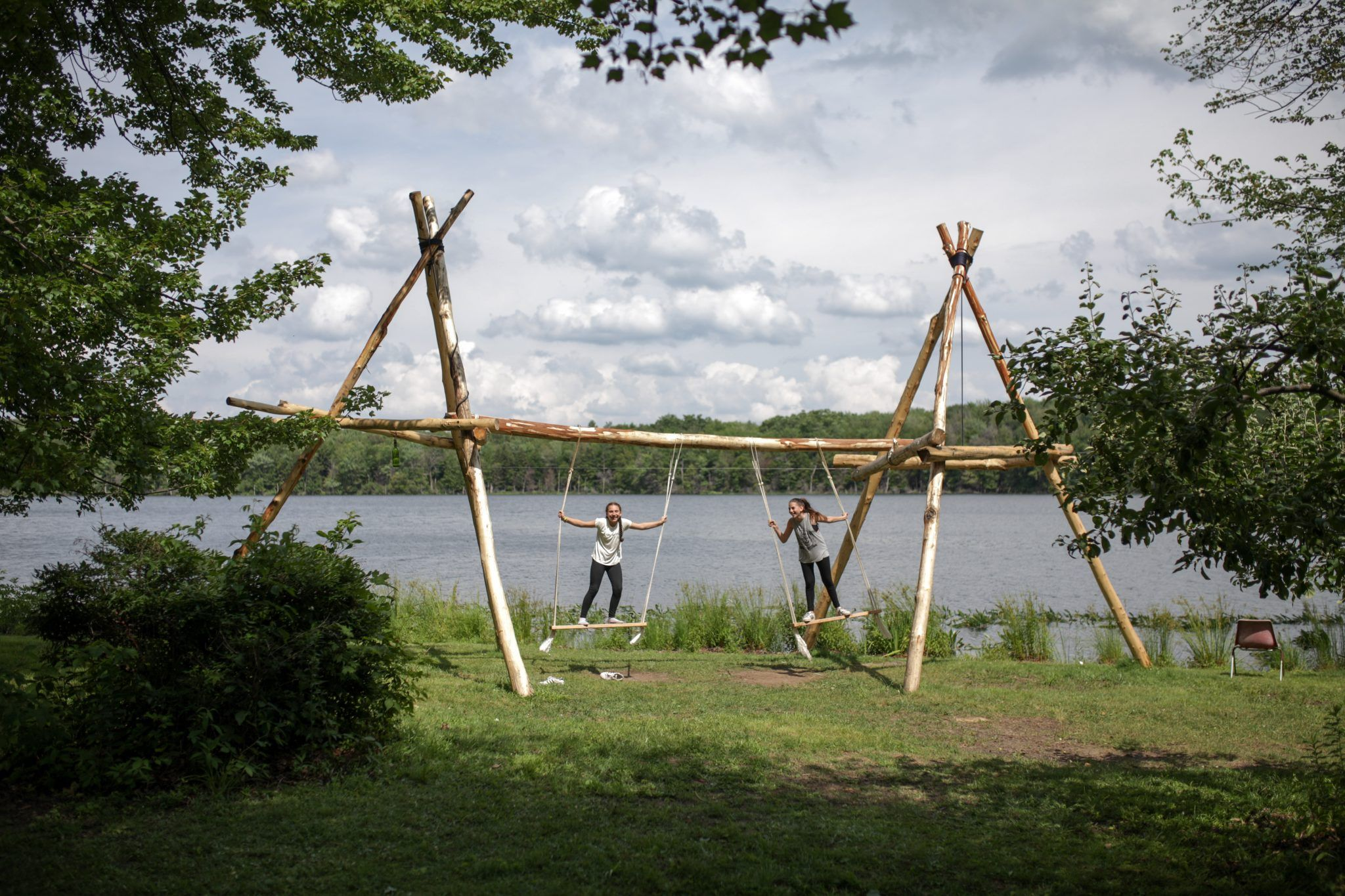 Photo of two female campers on a large swing set out by the lake