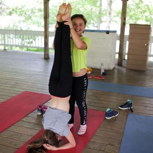 Two female campers, one supporting the other in a Yoga pose