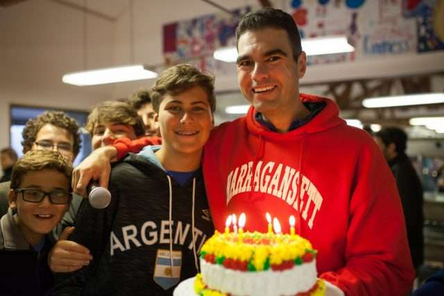 Isaac celebrating a camper's Birthday and presenting him with a cake