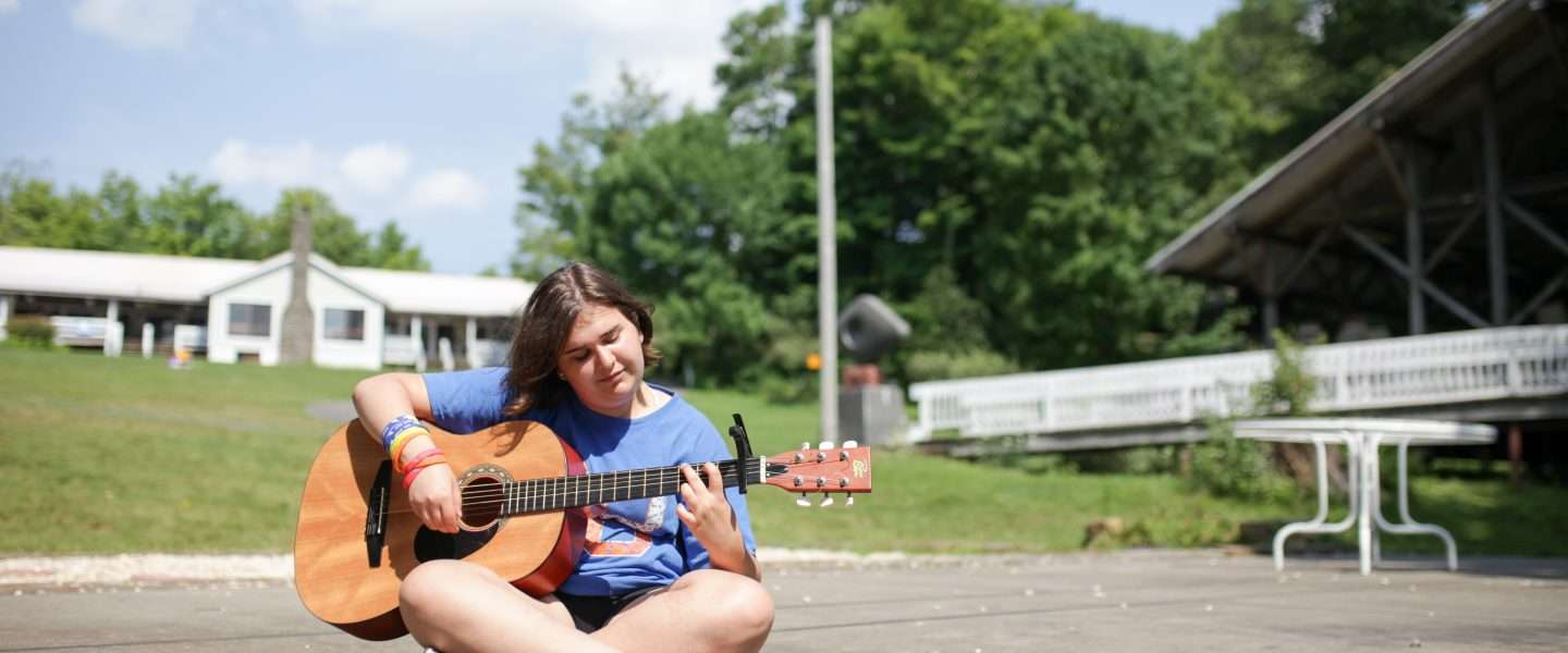 Female camper sitting outside playing guitar