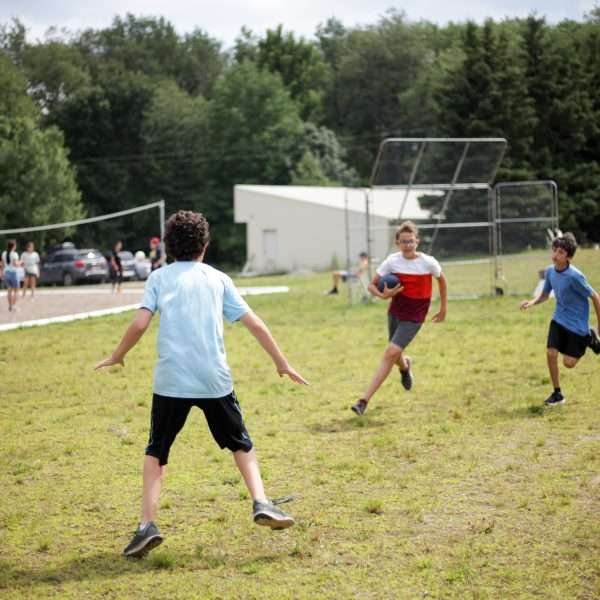 Three campers playing flag football