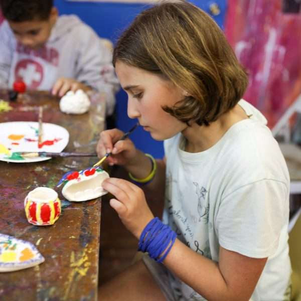 Female camper concentrating on painting ceramics