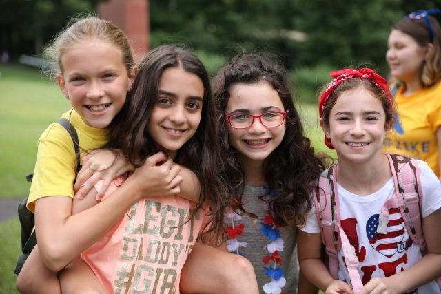 Group of young female campers with arms around each other