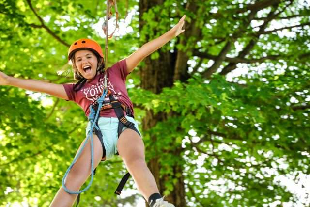 Female camper in trees on a high-wire