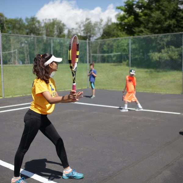 One of the camp counselors playing tennis with campers