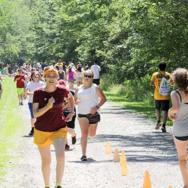Large group of campers running on a bright sunny day