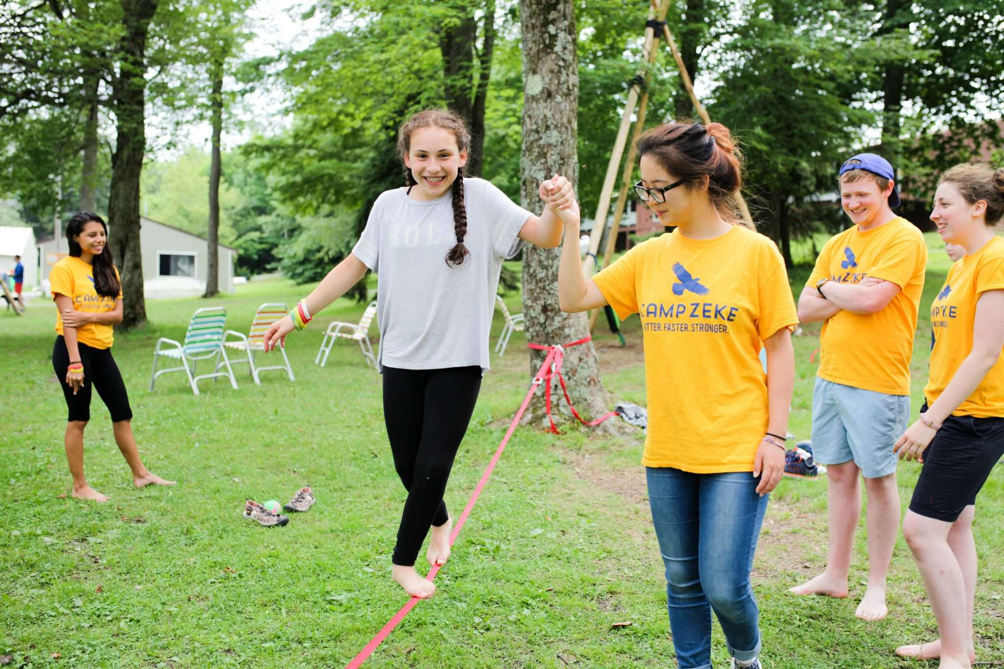 Girl practising the tightrope helped by a counselor
