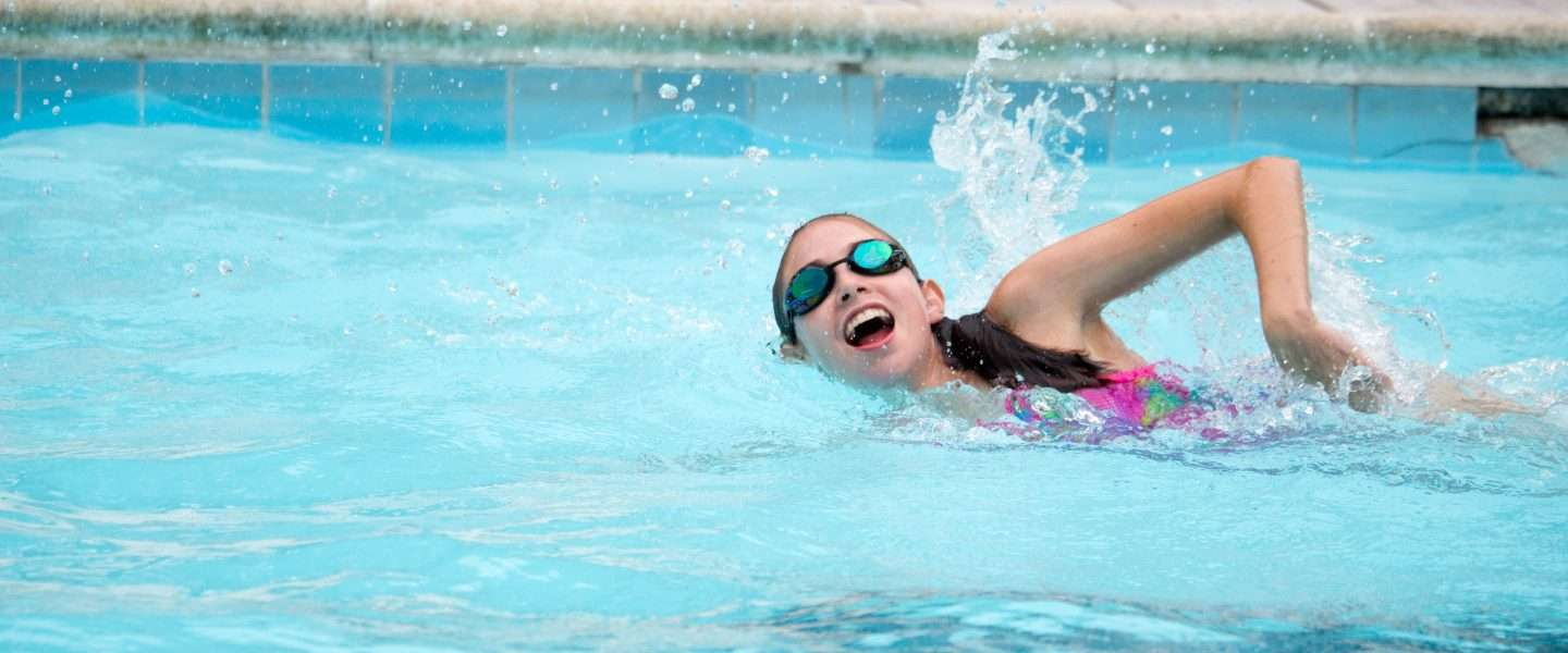 Female camper practising front crawl in the pool
