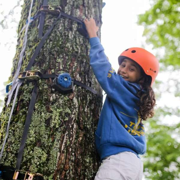 Female camper in a blue top climbing a tree with full safety gear