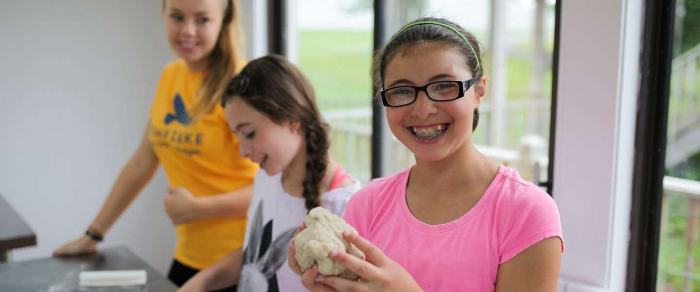 Two female campers kneading dough supervised by a counselor