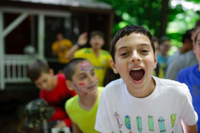 Group of male campers outside their bunks, one boy pulling a funny face directly to camera