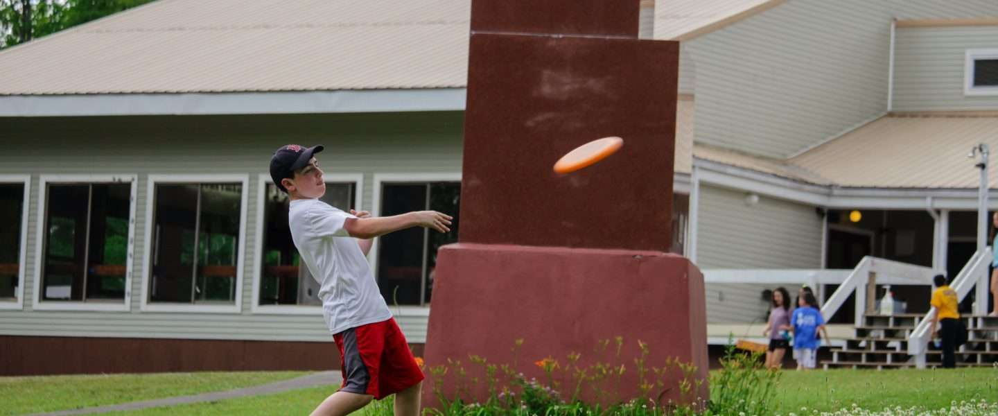 Male camper throwing a frisbee