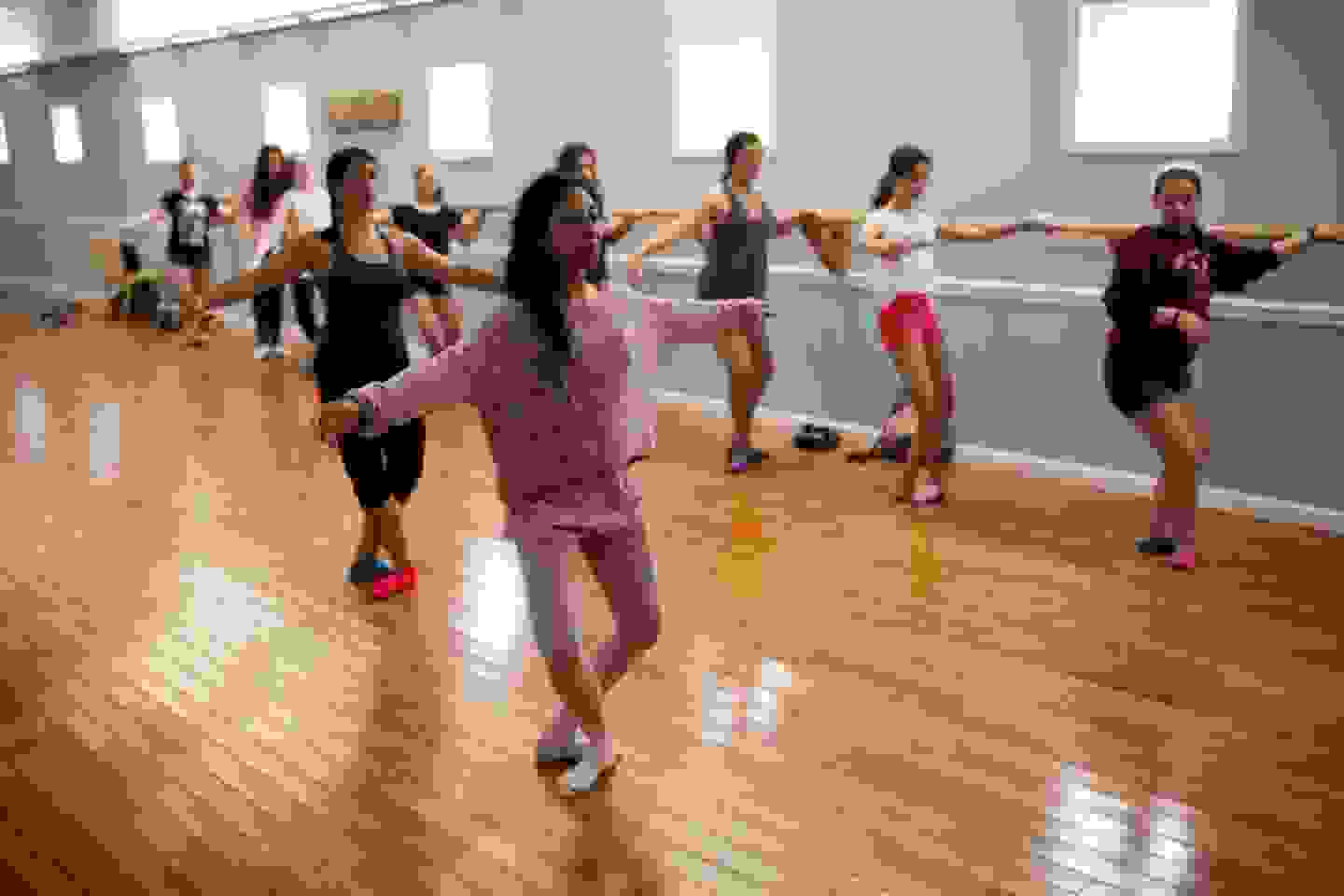 Group of female campers in the dance hall practising ballet
