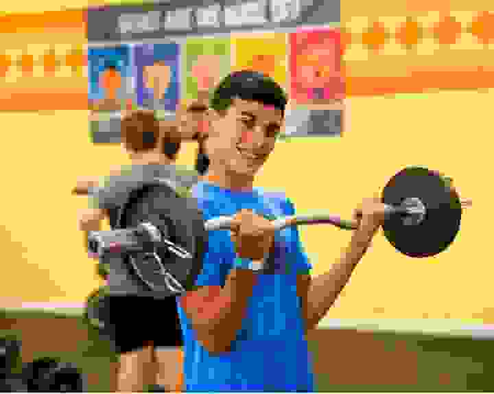 Camper lifting weights in the gym