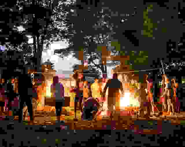 Group of campers around a camp fire at dusk
