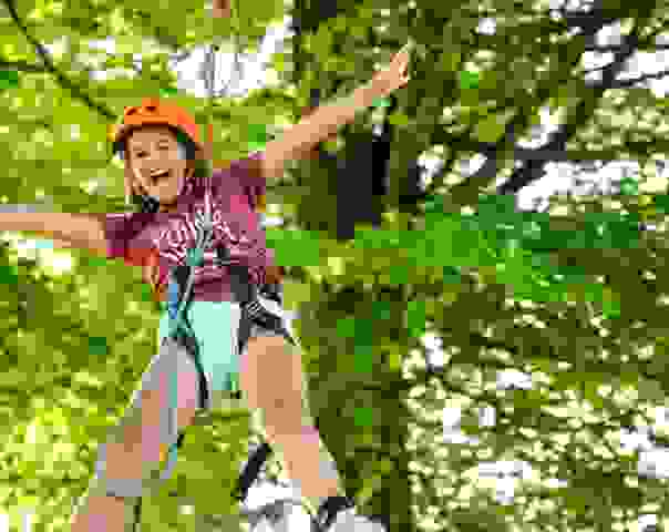 Photo of a female camper on a high-wire within trees
