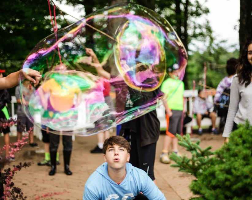 Campers outside playing with giant bubbles