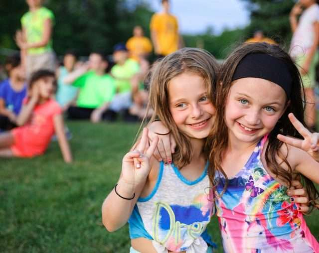 Two girl campers with arms around each other smiling