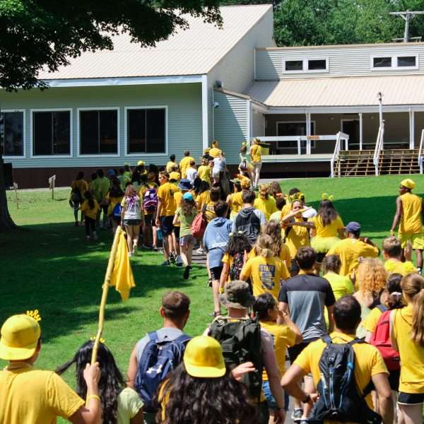 Campers being led to their dorms by staff, one long line snaking through the green grass surrounding the bunk buildings