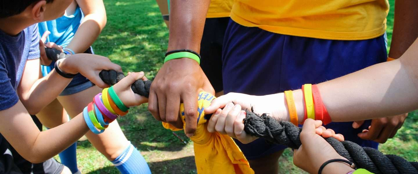 Camp staff working together during a tug-of-war