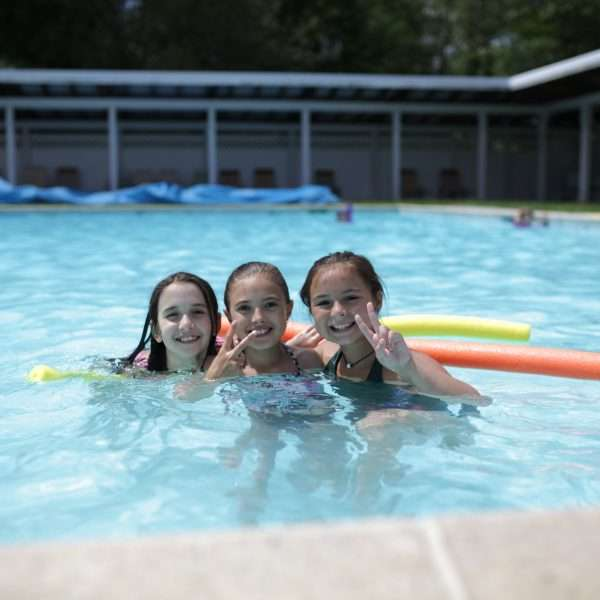 Three female campers in the Camp Zeke pool with flotation noodles