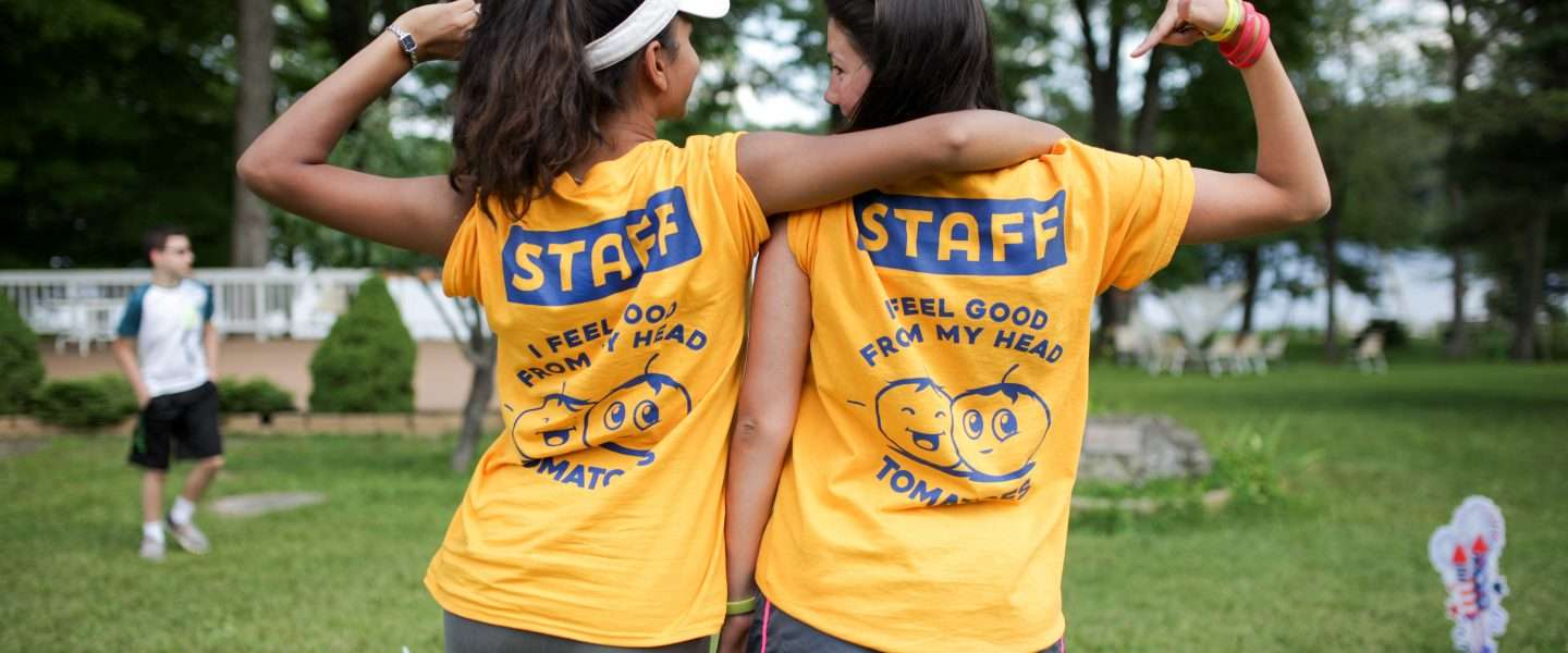 Two female staff from behind flexing arms wearing 'staff' t-shirts