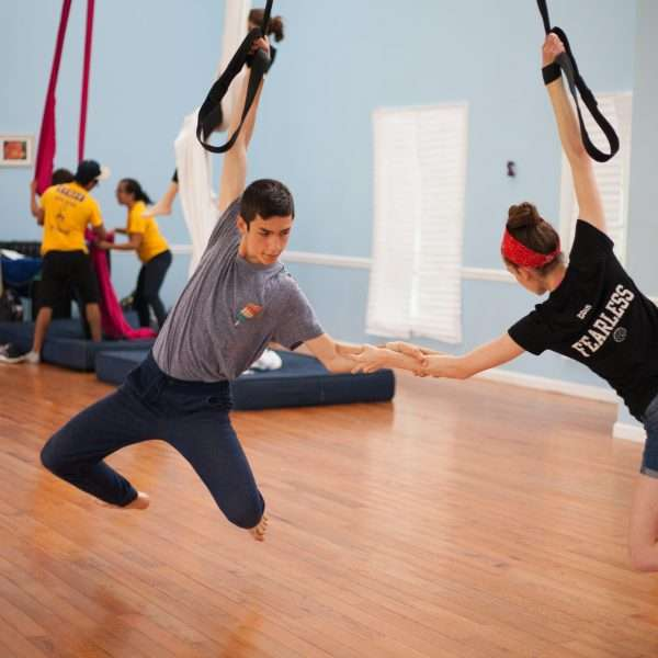 Two campers reaching out to each other while hanging from gym ropes
