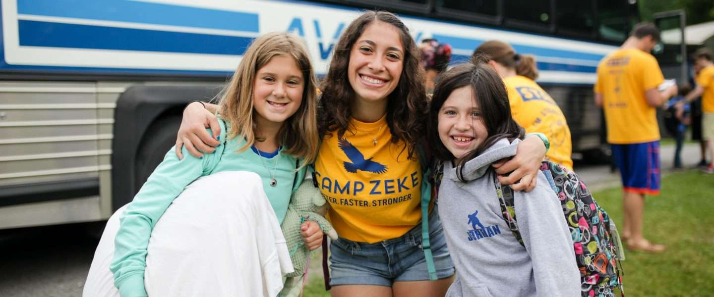 Camp Counselor hugging two new arrivals to camp