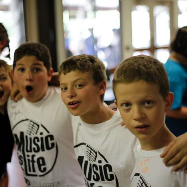 Group of young male campers with arms around each other singing