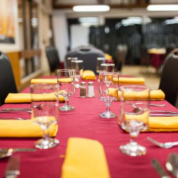 Photo of the dining room ready to receive diners, red table clothes set with cutlery and yellow napkins