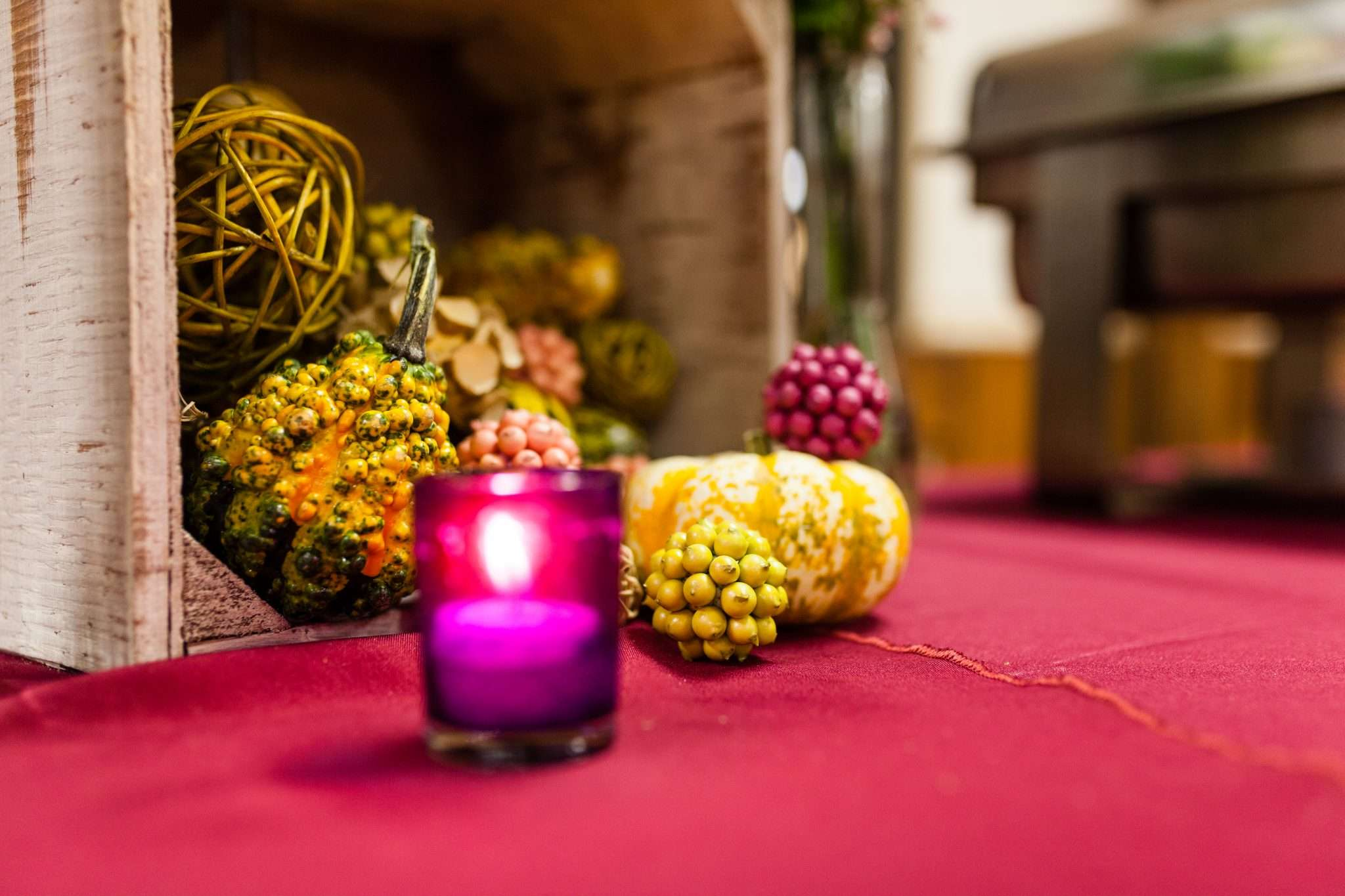 Close up photo of a candle and gourds used to decorate a table