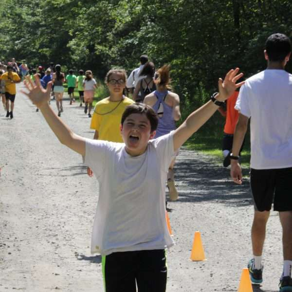 Large group of campers running toward the finish line of the Zeke 5K