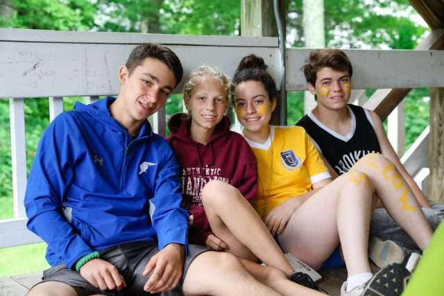 Four campers sitting outside their dorm relaxing