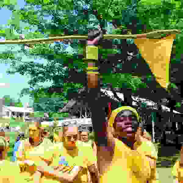 Camp staff all in yellow following one staff member who holds aloft a flag