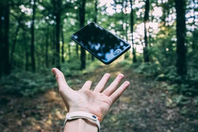 Hand throwing a smartphone into the forest