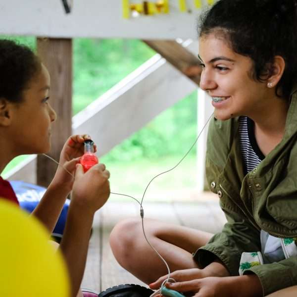 Teen leader listening to music with a younger camper