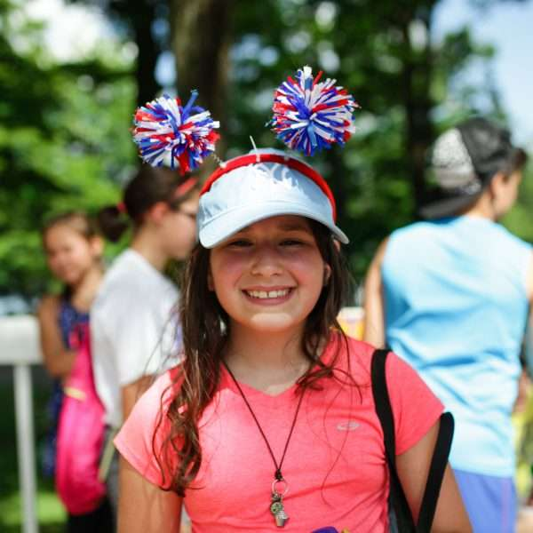 Female camper wearing a red, white and blue headband with pompoms