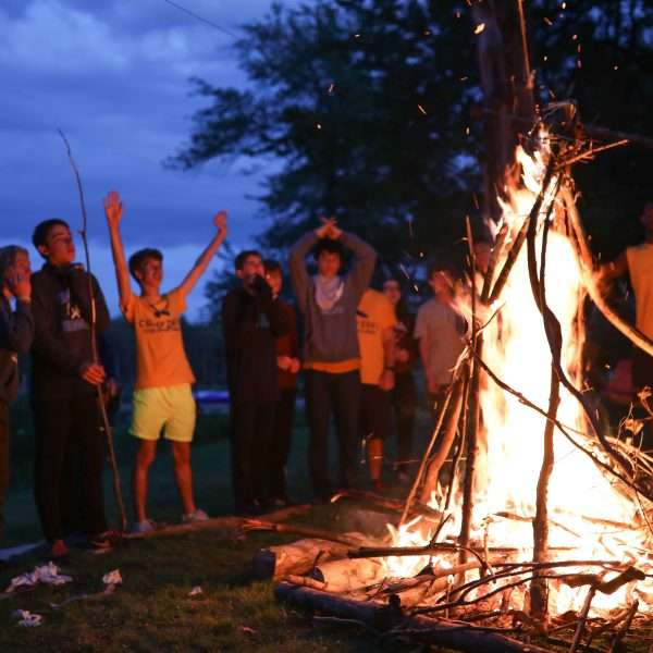 Group of campers around a roaring fire in the dark