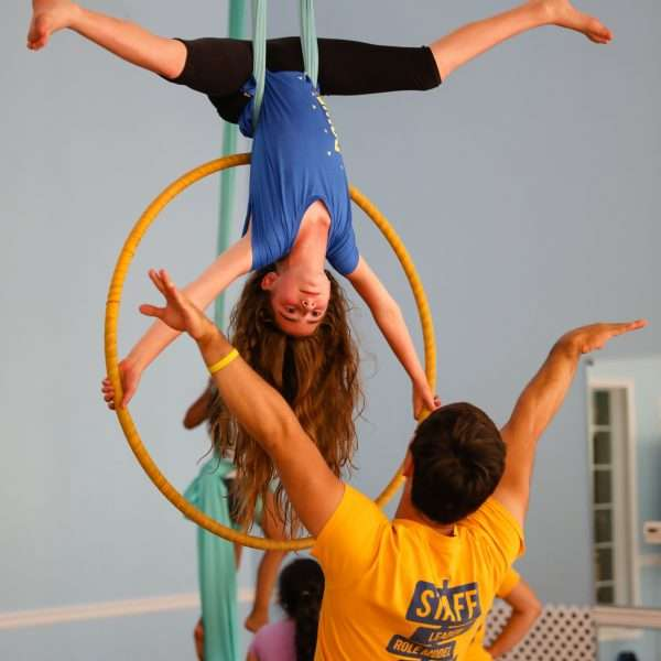 Female camper hanging from a suspended ring