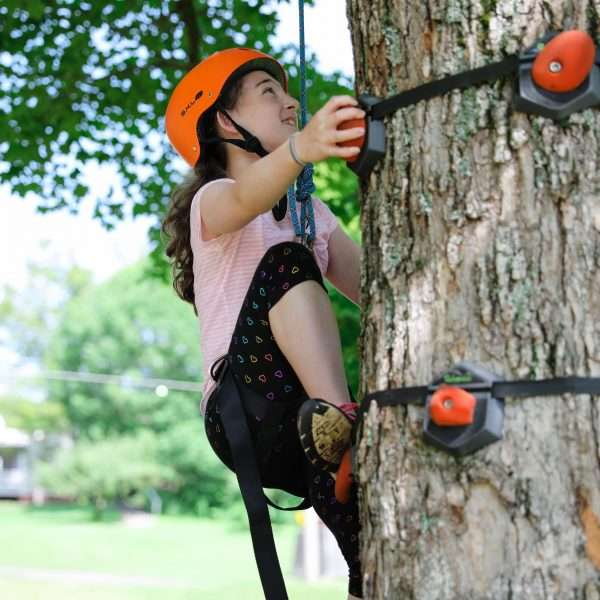Female camper climbing a tree in safety gear